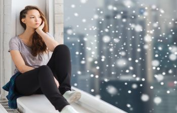 Girl Sitting in Window Sill While Snowing Atlanta GA